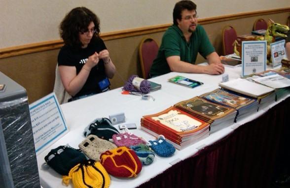 C et l'écrivaine CJ Ruby derrière l'étal de l'éditeur 4 Winds Fantasy Gaming à la convention MisCon 24